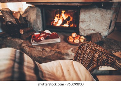 Everything ready for knitting with Christmas ornaments by the fireside. Handmade gifts for family. Cozy relaxed magical atmosphere in a chalet house decorated for Christmas. Holiday concept.