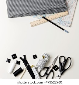 Everything for sewing in black and white. Fabric and thread, zipper and buttons, scissors and centimeter, pencil and ruler.