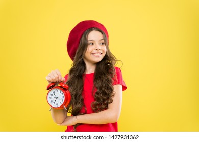 Everything is under control. Define own rhythm of life. Schedule and time. Set up alarm clock. Child little girl hold red clock. Always on time. It is never too late. Controlling personal time.