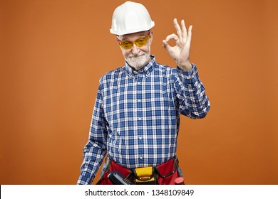 Everything is under control. Portrait of eldelry mature Caucasian handyman with thick beard wearing safety helmet and tool belt, making ok gesture, saying that he will fix broken leaky faucet