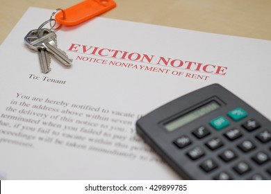EVICTION NOTICE WITH KEYS AND CALCULATOR IN BACKGROUND