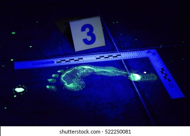 Evidence of footprint on place of crime in bathroom under UV black light