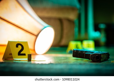 Evidence is marked with evidence markers on the floor of a home. A knocked over lamp lays nearby.
