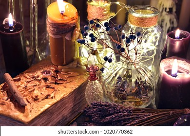 Evil book with black candles, glass bottles, and herbs on witch table. Occult, esoteric and divination concept.