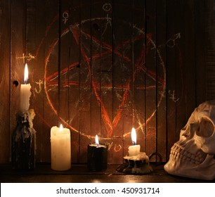 Evil candles and scary skull against wooden background with bloody pentagram.  Halloween concept, black magic ritual or spell with occult and esoteric symbols, divination rite