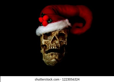 Evil Christmas Skull. Human Skull with a Santa Claus Hat. Isolated on black. Room for text. Evil Claus.