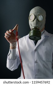 Evil and creepy medical experiment concept, a scary doctor in gas mask wearing bloody gloves with a battery booster jumper cable on dark background