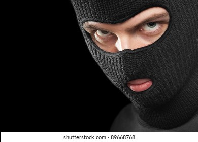 Evil criminal in a mask looking at the viewer; isolated on black background, copy space on the left.