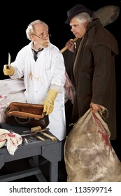 Evil doctor brandishing cleaver exchanges glances with grave robber over bloody corpse. Stage effect, isolated on black background, spot lighting.
