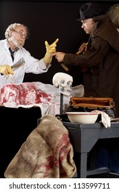 Evil doctor interacts with grave robber over bloody corpse. Stage effect, isolated on black background, spot lighting.