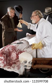 Evil doctor reaches over bloody corpse and pays grave robber, who tips hat. Stage effect with dark background, spot lighting.