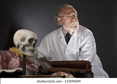Evil doctor with surgical tools and bloody corpse. Sinister expression, dark background with dramatic low angle spot lighting. Horizontal, copy space.