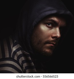evil dramatic portrait of a man in a hood on a black background