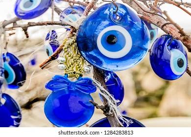 Evil eye bead blue amulet hanging on a tree and defocused blurred amulets on the background in Kapadokya, Turkey called in turkish nazar boncugu or nazarlık