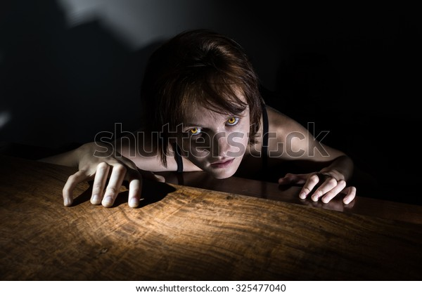Evil girl with glowing yellow eyes crawling to you from the darkness