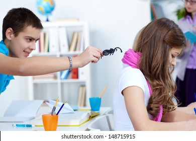 Evil lad holding black spider while going to frighten his classmate at lesson