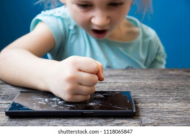 evil little girl blows her fists on a smartphone, breaks it