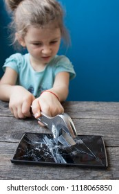 evil little girl breaks a smartphone with a wrench