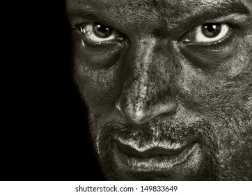 Evil man showing terror emotion and darkness in the intense eyes and sarcasm in the smile. In Black and White.