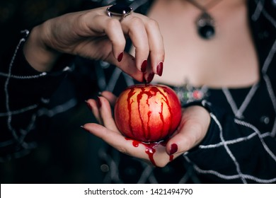 Evil Queen in a black dress with a red apple in their hands. Bloody apple