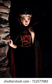 Evil queen with a crown in a fantastic portrait - Beautiful mystical princess in a dark cape Dracula. Halloween concept, costume party.