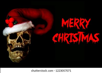 Evil Santa Skull with Red Santa Hat. Isolated on black. Room for text. Red text reads Merry Christmas.