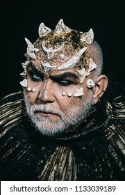 Evil underworld king with thorns on face and white beard wearing dark metallic outfit isolated on black background. Demon head with angry look, fantasy concept.