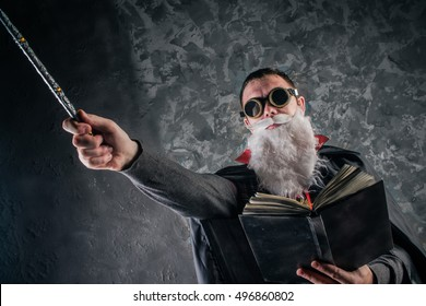 evil wizard Merlin conjures and casts a spell, raising his wand, a young man dressed in a stimpack Halloween hipster style