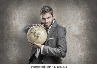 evil young business man holding a world globe against a grunge wall