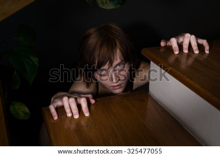 Evil zombie girl with glowing eyes crawling to you from under the stairs