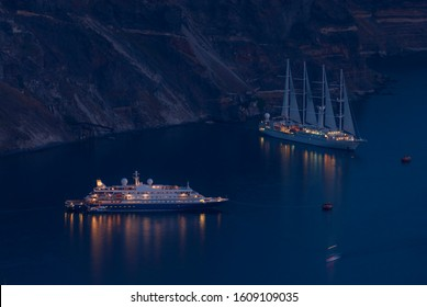 evocative night of a cruise ship and a sailing ship with the lights on, anchored in the night, below the coast of the island of Santorini, Cyclades Islands, Greece, Aegean Sea, Europe