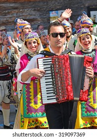 EVOLENE, SWITZERLAND - AUGUST 11:Turkish acordeonist and dancers from Bozdaglar in the CIME mountain culture Festival: August 11, 2015 in Evolene, Switzerland