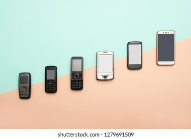 evolution of cell phones. Technology development telephone and pda concept. Vintage and new phones. Top view. Telephone communication progress, mobile classic device. Blue and apricot shade background