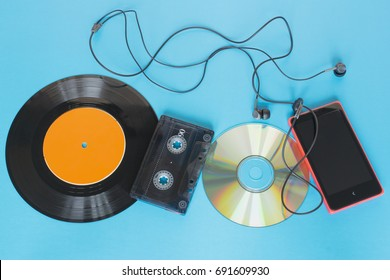 Evolution of technology concept, vinyl record, tape, disk and smartphone with headphones on the blue background.