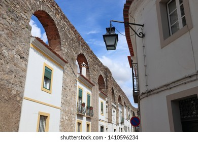 Evora town in Portugal. UNESCO World Heritage Site. Prata Aqueduct with homes beneath arches.