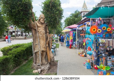 Evpatoria, Crimea, Russia - July 4, 2018: Wooden figure of a bogatyr and street trade in beach accessories near the U Lukomorye water park in the resort town of Evpatoria, Crimea