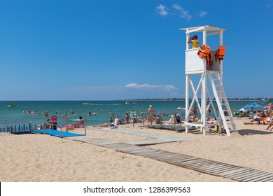 Evpatoria, Crimea, Russia - July 4, 2018: Ramp for arrival into the sea of disabled people and a rescue tower on Rodnichok beach in the resort town of Evpatoria, Crimea