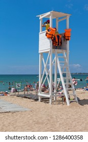Evpatoria, Crimea, Russia - July 4, 2018: A rescuer observes through binoculars from a tower on Rodnichok beach in the resort town of Evpatoria, Crimea