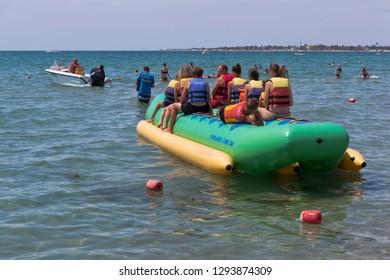Evpatoria, Crimea, Russia - July 5, 2018: Inflatable banana with passengers on the Rodnichok beach in the resort town of Evpatoria, Crimea