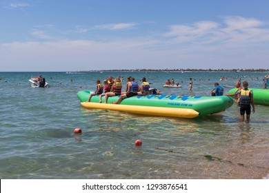 Evpatoria, Crimea, Russia - July 5, 2018: An inflatable banana with passengers ready for a water attraction on the Rodnichok beach in the resort town of Evpatoria, Crimea