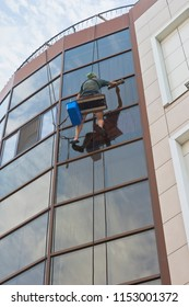 Evpatoria, Crimea, Russia - June 29, 2018: Industrial climber washes windows of an office building
