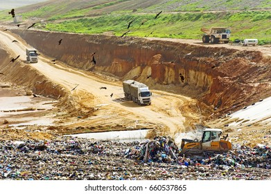 Evron, Israel - May 15 2012: Meduim size landfill site with compactor,trucks and the pit