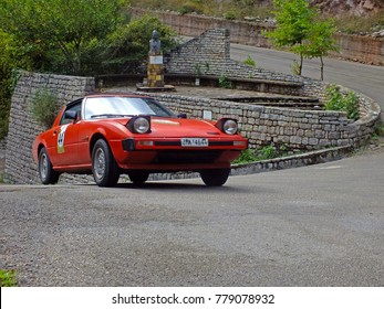 EVRYTANIA, GREECE, SEPTEMBER 2014. Red classic car Mazda RX7, made in Japan in 1981, participating in the 43rd International Rally of Classic Car Club of Greece-FILPA in central Greece