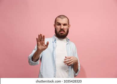 Ew. It's so gross. Young man with disgusted expression repulsing something. Disgust concept. Young emotional man. Human emotions, facial expression concept. Studio. Isolated on trendy pink color