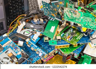 E-waste pile from discarded laptop parts. Connectors, PCB, notebook keyboards. Colorful background from PC components. Idea of sorting, recycling and disposal of electronic waste. Full depth of field.