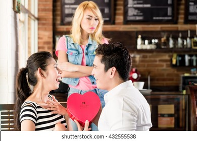 ex girlfriend being jealous on couple in cafe watching Asian woman and man flirting