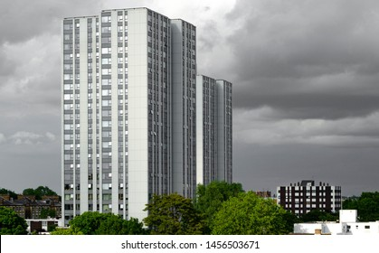 Ex local authority social housing high rise flats in north London, UK. Tower blocks stand tall basking in the late evening sun set against ominous black rain clouds.