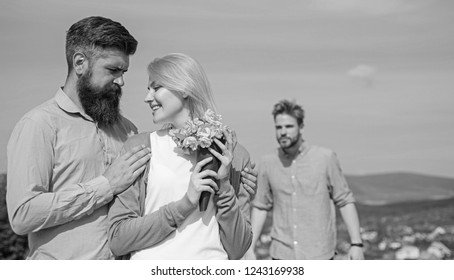 Ex partner watching girl starts happy love relations. Couple in love dating outdoor sunny day, sky background. Leave past behind. Couple with bouquet romantic date. Ex husband jealous on background.