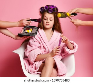 Exacting young lady teen girl in spa salon evaluates makeup offered to her while making hair style and manicure. Beauty concept on pink background