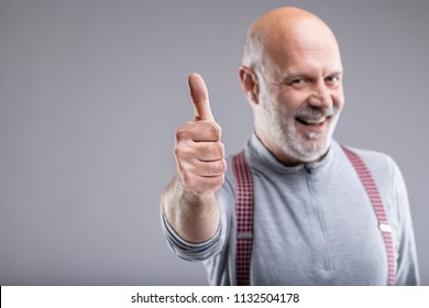 exaggerated thumb up and smile by a mature man with suspenders